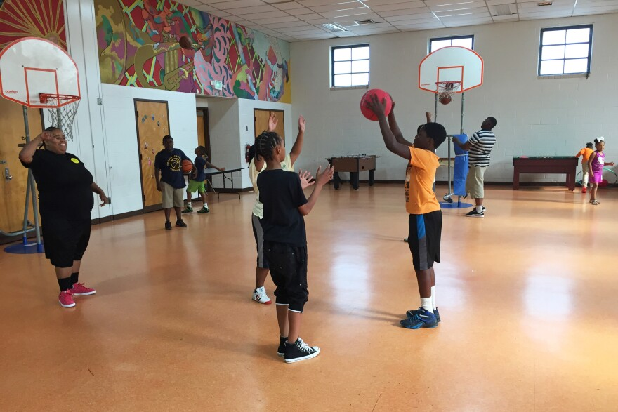 "Zyon Height (in orange) passes the ball during a game of basketball at the Lillian S. Jones Recreation Center. ""We are mom, dad, aunt, cousin,"" says Brandi Murphy, the center's director. ""They come here to get what they don't have at home."""
