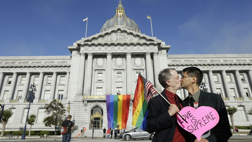 Gay rights advocates John Lewis (left), and his spouse Stuart Gaffney kiss across the street from City Hall in San Francisco, on Friday following a ruling by the U.S. Supreme Court that same-sex couples have the right to marry nationwide.