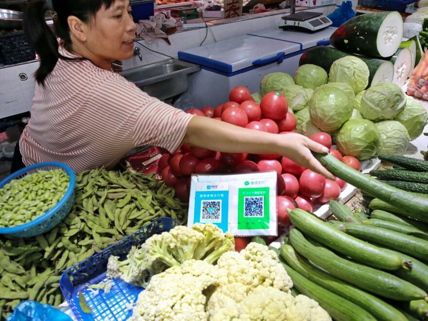 Alipay and WeChat QR codes for online payment are displayed at a vegetable stall in Nantong in China's eastern Jiangsu province. Now China's central bank is preparing to test a digital currency.
