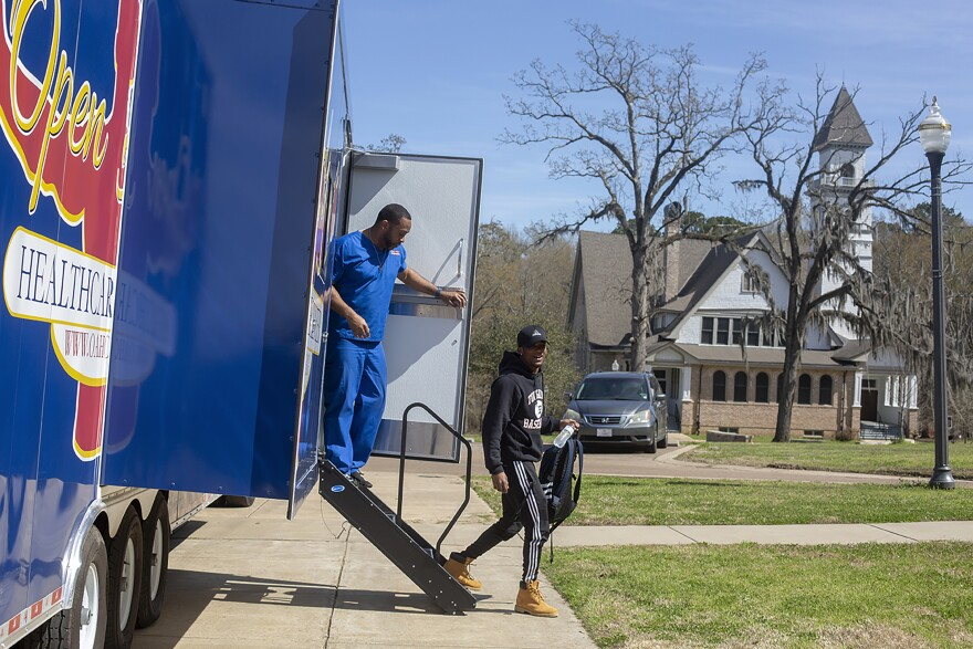 Gerald Gibson (left), manager of the Open Arms Mobile Health Clinic talks with Javier Heniquez, a student at Tougaloo College, as he leaves the clinic.