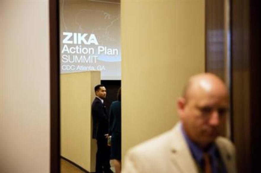 A graphic is displayed on a screen as attendees wait for a seminar to begin at a one-day Zika summit at the Centers for Disease Control and Prevention Friday, April 1, 2016, in Atlanta.