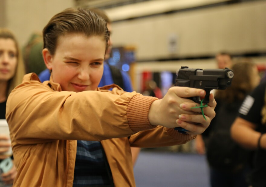 Francis Bandy holds a gun with both hands, squinting as she aims it in front of her.