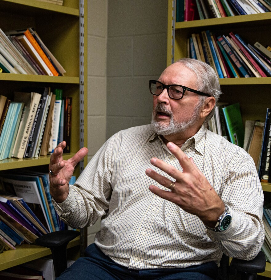 Professor Dell De Chant sits between two book cases and gestures while speaking.