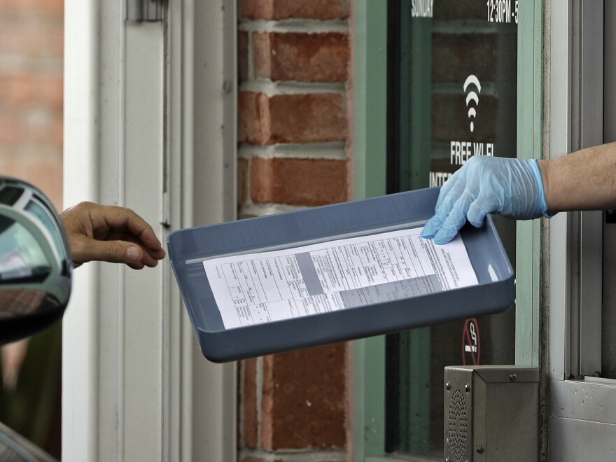 A Hillsborough County Library employee hands unemployment paperwork to residents in Tampa, Fla.