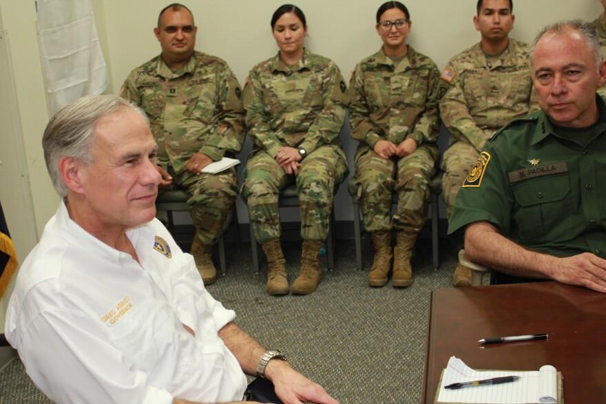Texas Gov. Greg Abbott (left) and Manuel Padilla, chief of the Rio Grande Valley Border Patrol Sector, meet National Guard troops in Weslaco, Tex.