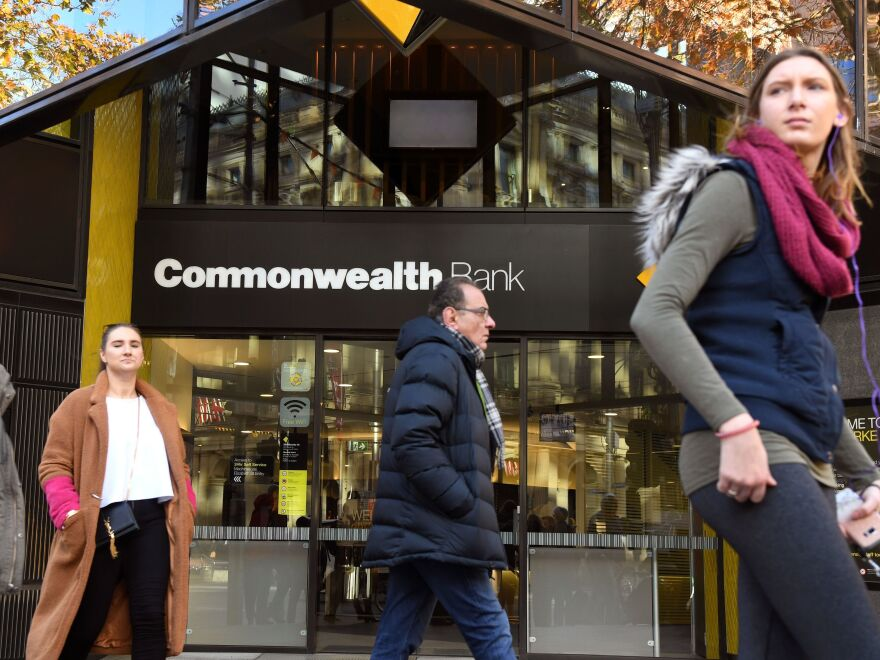 People walk past a branch of Australia's Commonwealth Bank in Melbourne on Monday. The Commonwealth Bank agreed to the largest civil penalty in Australian corporate history to settle claims it breached anti-money laundering and counter-terrorism financing laws.