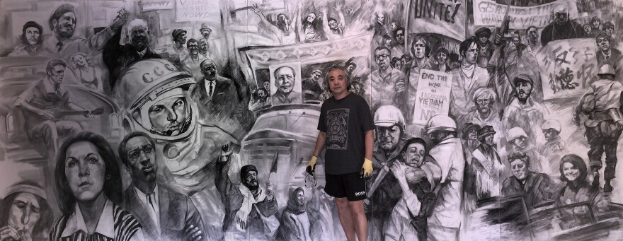 Yingxue Zuo stands in front of '60s - Cold War,' one of four murals in new show 'The Voice' at Southern Illinois University Carbondale.