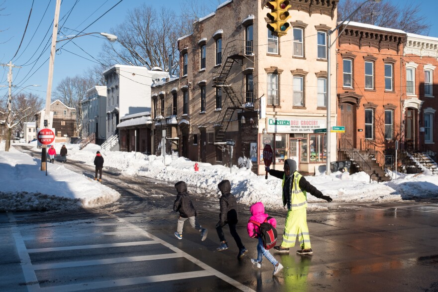 Children cross the road into Albany's West Hill neighborhood. While the neighborhood is close to the state Capitol building, many streets have boarded-up homes with red signs posted by the fire department. The signs indicate that there is potential the buildings could collapse.