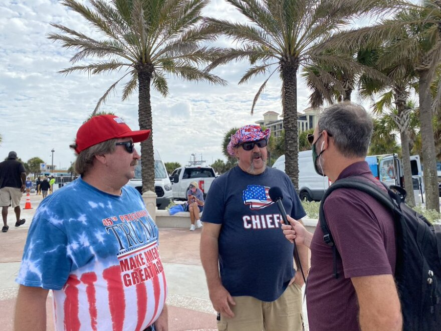 A masked reporter holding a mic interviews two unmasked men, one wearing a chiefs shirt and one wearing a Trump shirt.