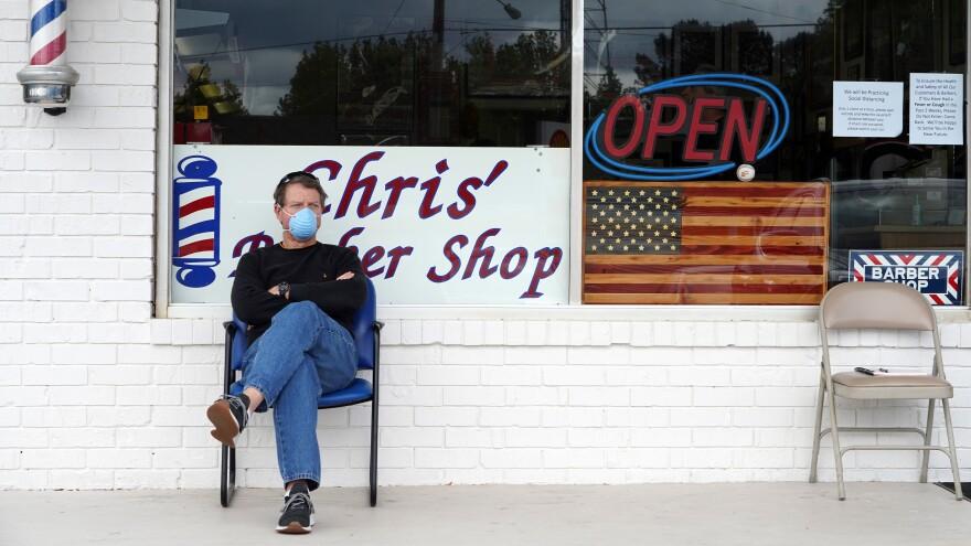 Dan Settle sits outside Chris' Barber Shop as he waits his turn for a haircut in Lilburn, Ga., on Friday.