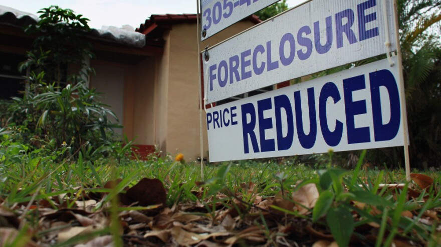<p>A foreclosure/price reduced sign stands in front of a home for sale on February 11, 2011 in Miami.</p>