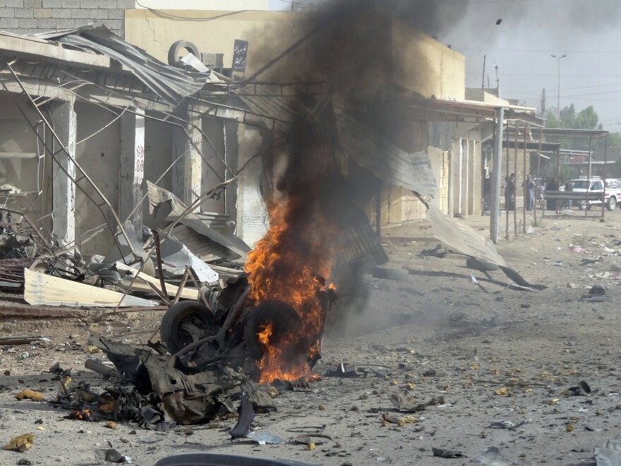 Smoke rises from the wreckage of a vehicle in Kirkuk, Iraq. A bomb in it exploded — one of a series of coordinated attacks today on Shiite Muslims across the country.
