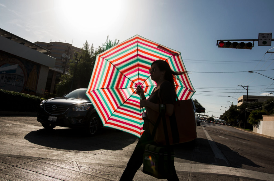 Woman walking in heat with umbrella to shield the sun