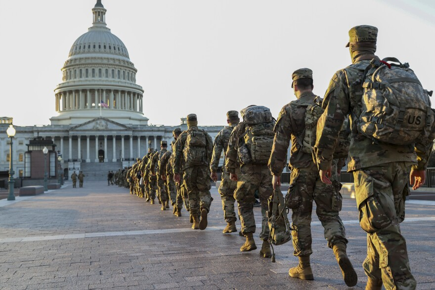 Members of the National Guard arrive at the U.S. Capitol on Tuesday to assist with security ahead of President-elect Joe Biden's inauguration. A new poll finds 58% of Americans think President Trump is to blame for the violence last week.