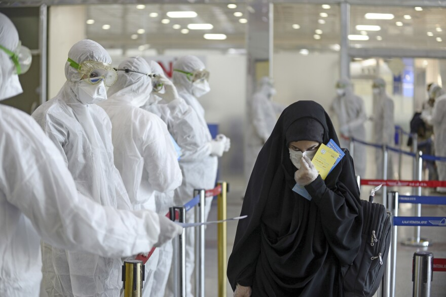 Medical staff in protective gear hand out information sheets about COVID-19 to Iraqi passengers returning from Iran at Najaf International Airport on March 5. Iraq has seen a serious outbreak of the virus.