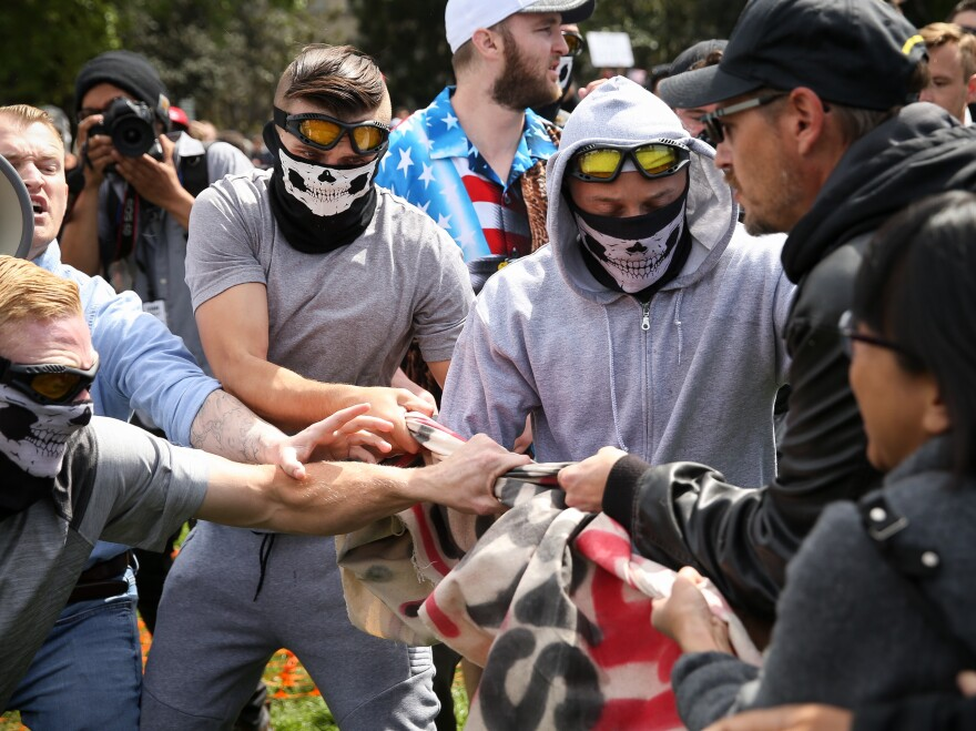 Rise Above Movement members wearing their skeleton masks pull away a counterprotester's flag at a Patriots Day rally last April in Berkeley, Calif. Four RAM members were arrested for violence at the rally and a string of others.