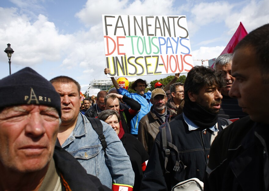 "Protesters in Paris, one carrying a banner declaring ""Slackers of all countries Unite,"" march against President Emmanuel Macron's overhaul on Tuesday."