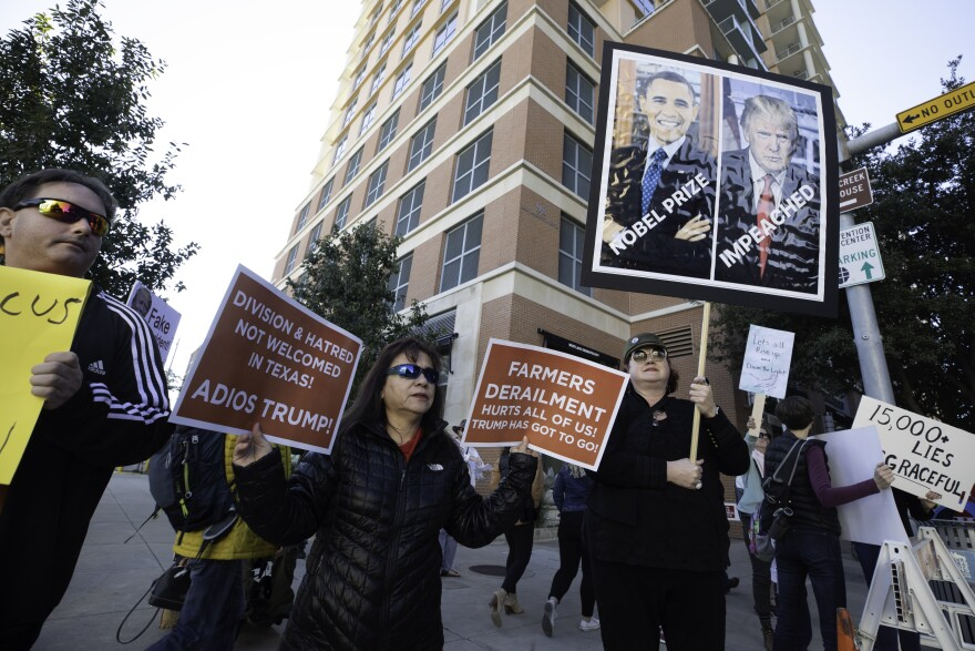 Protesters hold anti-Trump signs outside the Austin Convention Center.