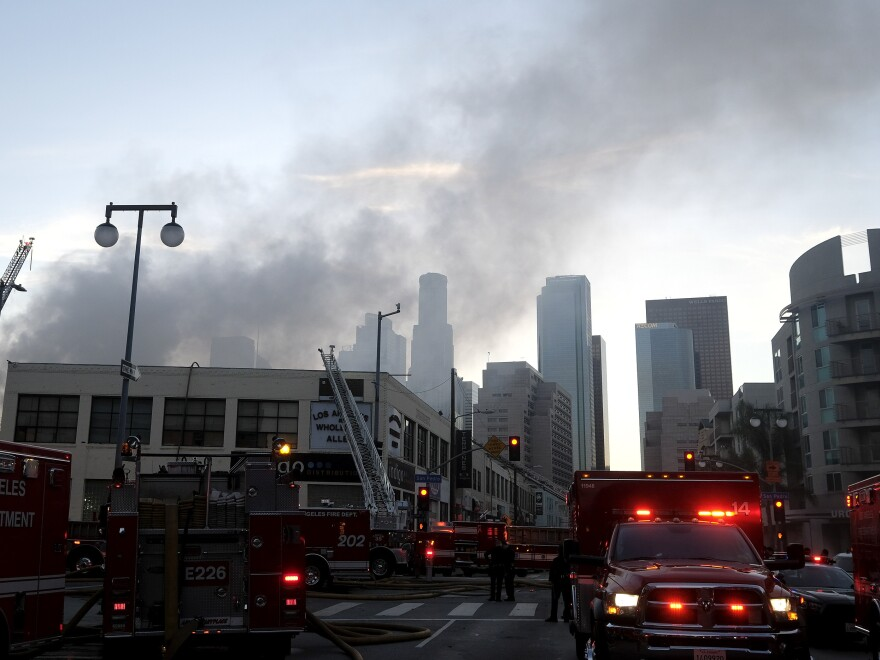 Smoke rises from the scene of a fire and explosion in Los Angeles on Saturday that injured 12 firefighters.