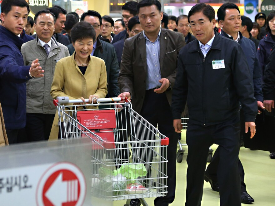 """South Korean President Park Geun-hye pushes a cart in a store in the capital, Seoul. In remarks Wednesday, North Korea referred to the """"venomous swish"""" of her skirt."""