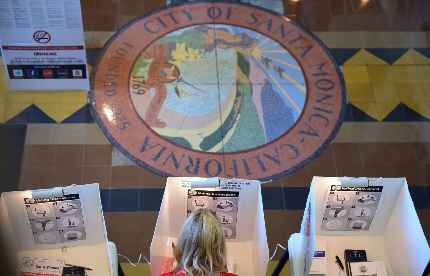 People vote at Santa Monica City Hall on Tuesday. Proposition 60, California's controversial ballot measure that would require adult film performers to use condoms, has been rejected.