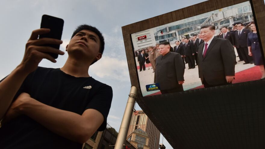 A man waits for a taxi in Beijing as news footage of Chinese President Xi Jinping (right) being greeted in Pyongyang by North Korean leader Kim Jong Un is shown on a large screen outside a shopping mall.
