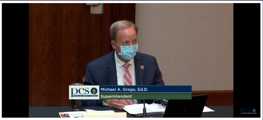 Superintendent Michael Grego wears a suit and mask as he talks at a microphone