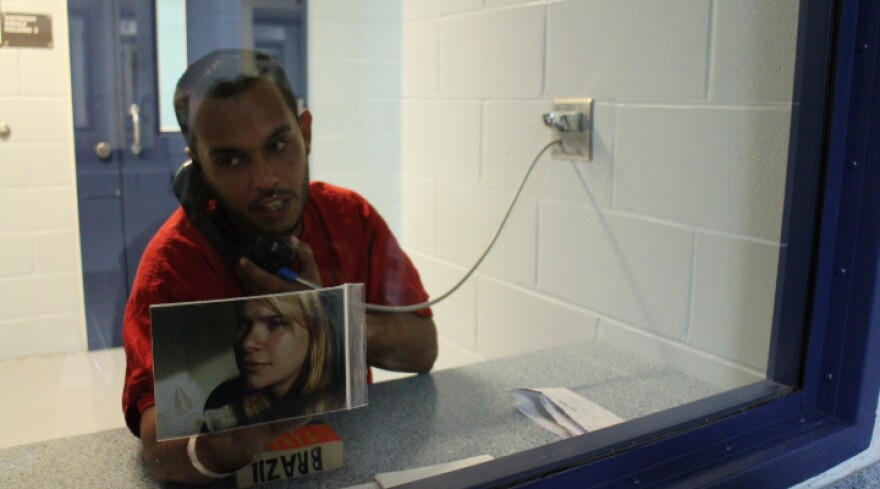 Danyel Ferraz, an immigrant detained at the Krome Service Processing Center, shows Peggy Mustelier photos of his children.