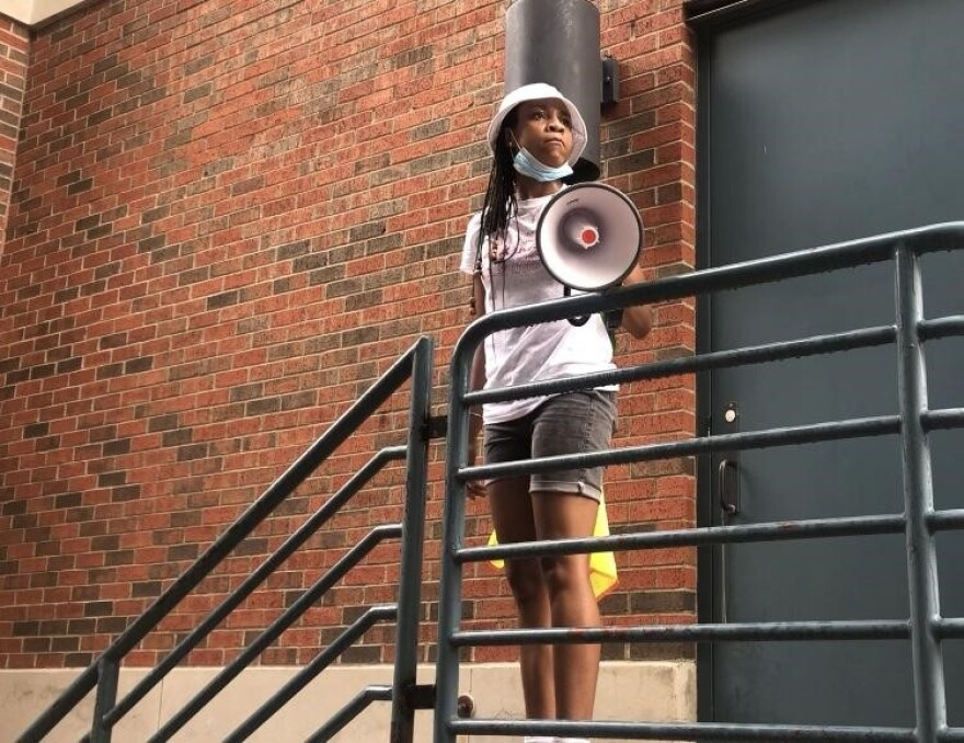 Photo of SMU student Tyne Dickson wearing a face mask pulled down and looking out at the crowd as she holds a bullhorn.