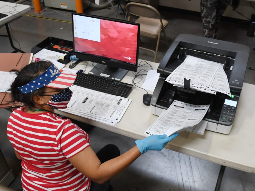An election worker scans mail-in ballots at the Clark County Election Department on Oct. 20 in North Las Vegas, Nevada.
