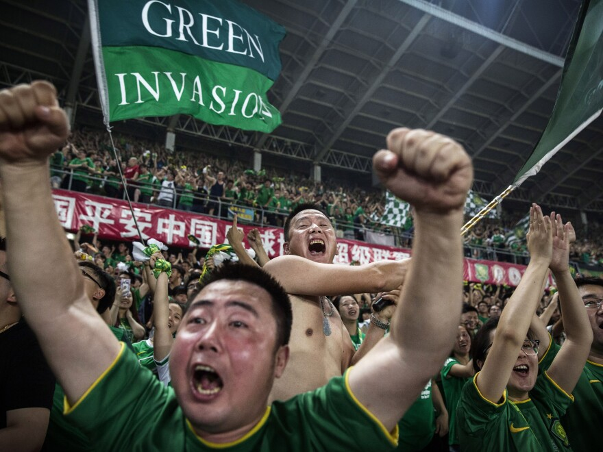 Fans of Chinese Super League club Beijing Guoan celebrate after a goal against Chongqing Lifan on June 28, 2015.