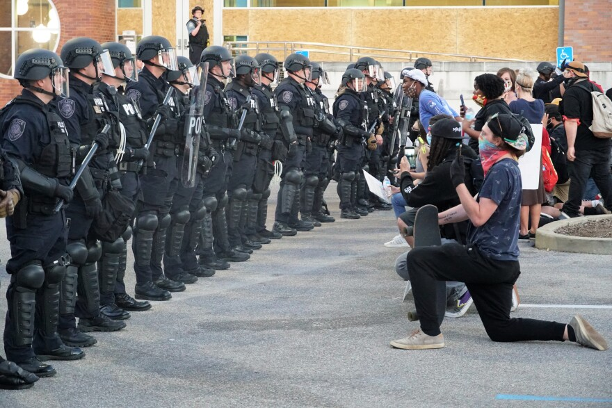 Demonstrators kneel in front of police officers at a protest in Ferguson on May 31, 2020.