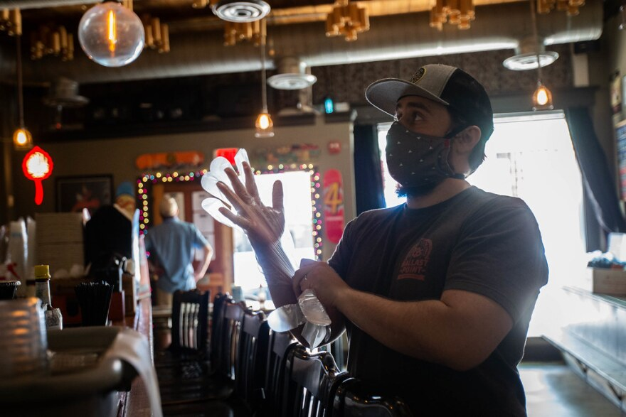 Glen Kruth puts on gloves before making a sandwich for a customer at Dive Bar and Lounge on May 21. Despite being allowed to reopen, the bar is sticking to takeout for now.