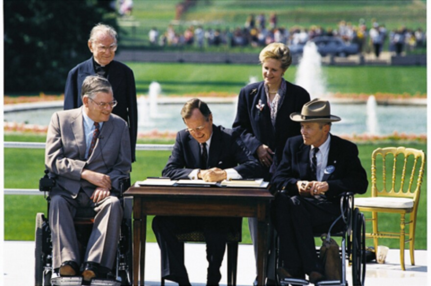 President George H.W. Bush Signs The Americans with Disabilities Act in 1990.