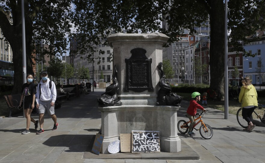 People look at the pedestal of the toppled statue of Edward Colston in Bristol, England, on Monday, following the downing of the statue on Sunday at a Black Lives Matter protest. Colston was a notorious slave trader — a badge of shame in what is one of Britain's most liberal cities.