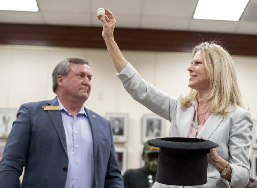 Outgoing Dickinson, Texas, mayor Julie Masters, right, holds up a ping-pong ball as Sean Skipworth looks on.