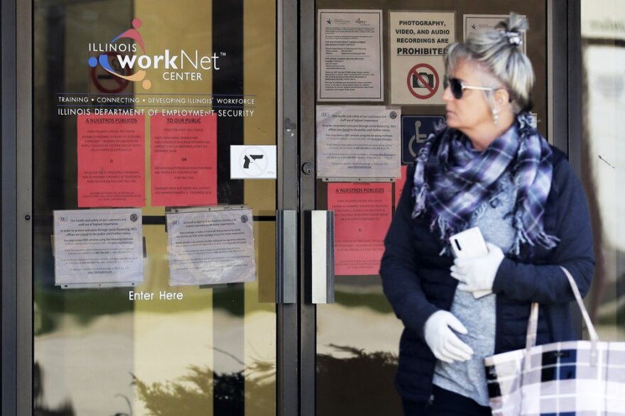 A woman looks to get information about job application in front of IDES (Illinois Department of Employment Security) WorkNet center in Arlington Heights, Ill., Thursday, April 9.
