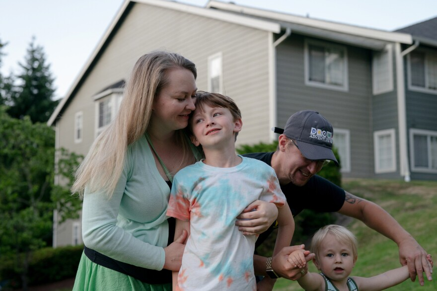 The Vodolazov family, who emigrated from Russia, stand outside their home in Bellevue. Their apartment is open and bright, with new appliances. The rent is $2,600 a month, mostly covered by the voucher.