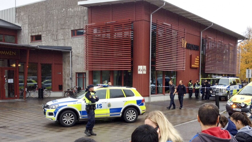Swedish police secure the area outside a primary and middle school in Trollhattan in southwestern Sweden, where a masked man armed with a sword killed one teacher and injured several other people before being shot and arrested by police.