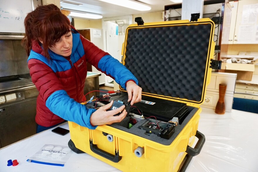 Scientist Jessie Creamean and her portable aerosol sampler in the lab on the research vessel Akademik Fedorov.
