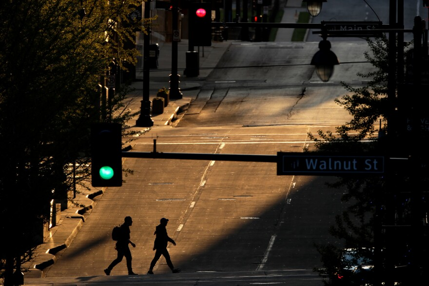 People cross an empty downtown Kansas City, Mo., street on Wednesday while stay-at-home orders continue in the state and much of the rest of the United States as part of an effort to curb the spread of the new coronavirus.