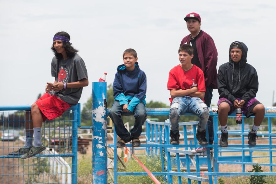 Photo of spectators on fence.