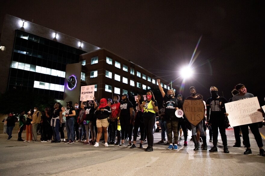 Photo of protesters in a line blocking the intersection in front of Dallas Police Headquarters.
