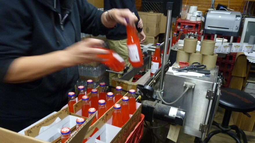 Bottles of Squamscot Soda get a label inside the company's factory in Newfields, N.H. (Todd Bookman/NHPR)