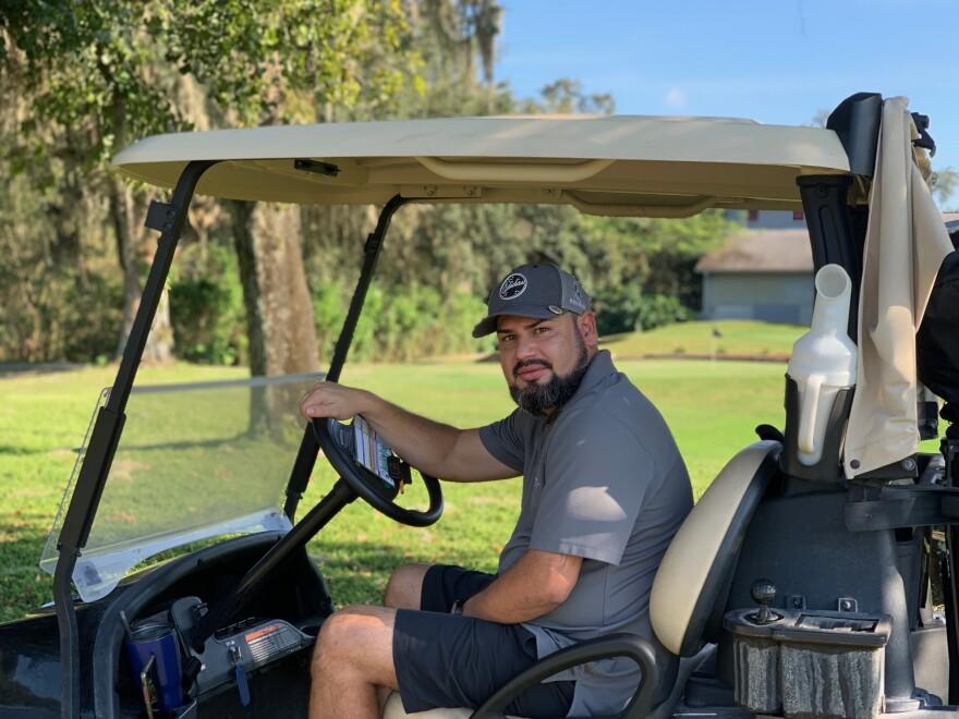 Veteran Roberto Cruz sits in a golf cart.