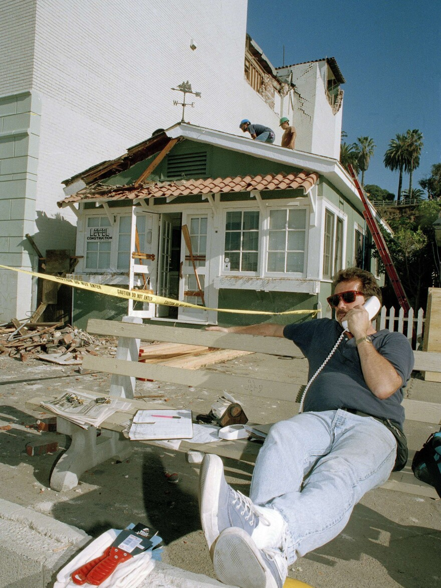 After the 1994 earthquake, Jim Barden of Santa Monica, Calif., conducts his business over the phone as workmen begin to repair his earthquake-damaged home. California homeowners may have become a little too nonchalant about earthquake insurance, authorities fear.