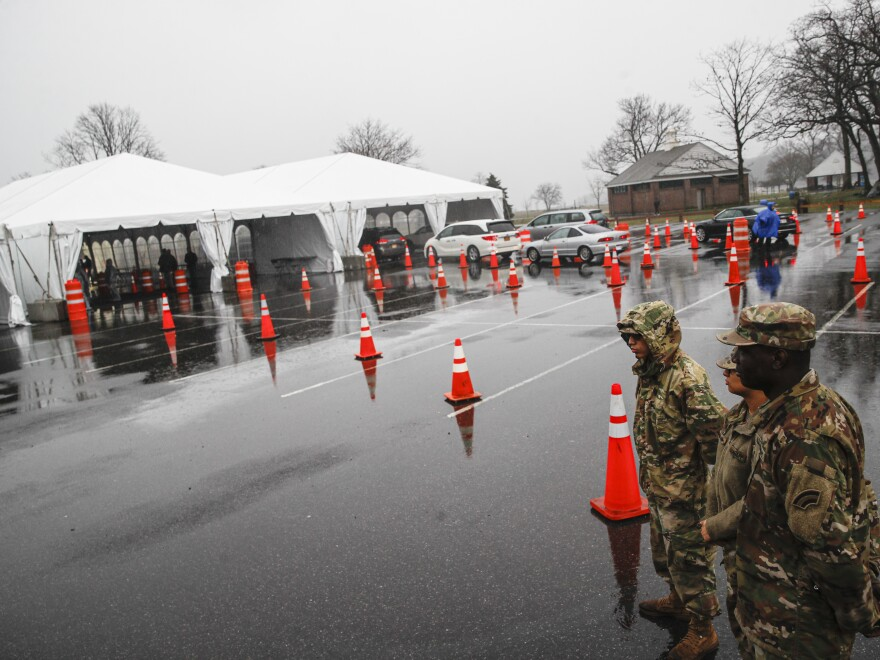 National Guard personnel stand beside a line of motorists waiting for coronavirus testing in New Rochelle, N.Y., on Friday. Major retailers such as CVS, Target and Walmart are pledging to set up drive- through test sites in some of their parking lots.