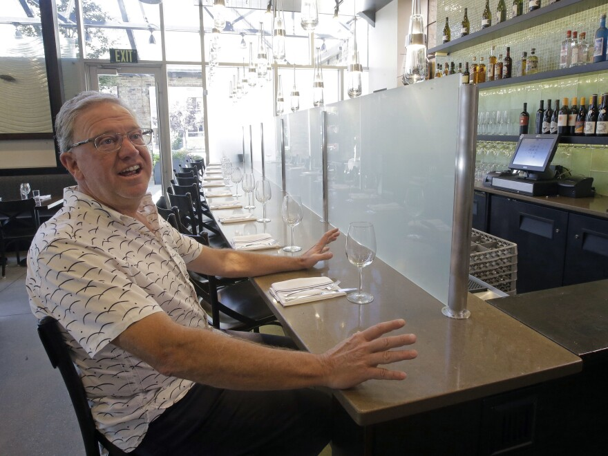 Salt Lake City restaurant owner Joel LaSalle sits in front of a once-mandatory partition that prevented customers from seeing their alcoholic drinks being mixed and poured. New state legislation meant he could remove the partition on Saturday.