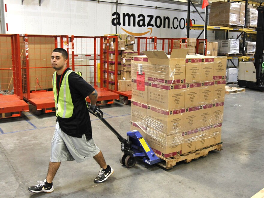 Humberto Manzano Jr. moves a pallet of goods at an Amazon.com fulfillment center in Phoenix in 2010. Amazon has endorsed a bill making its way through the Senate that would require more online retailers to collect sales tax.