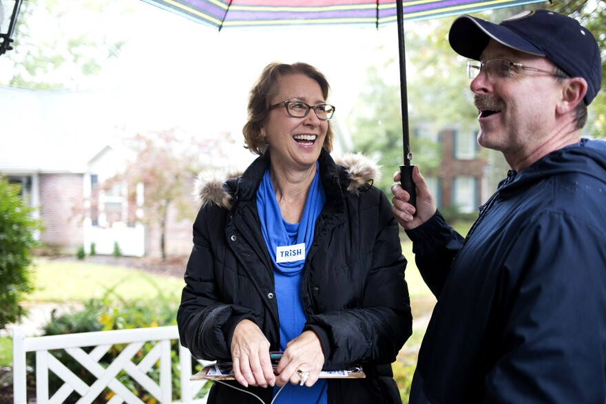 Trish Gunby and her husband, Mark, speak with a voter while canvassing in the 99th district. Oct. 26, 2019